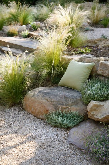 A pillow tossed on this boulder creates a powerful invitation to sit and enjoy the garden. Remove the pillow and the seating disappears into the stone retaining wall behind it.