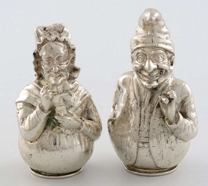 A pair of cast Victorian novelty silver Punch and Judy pepper pots,by E. Stockwell, London 1887