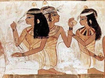 fragrance & Ancient Egypt. Those are cones of wax and perfume on their heads (the hair probably wigs). The wax would melt from their body heat over the course of the evening, releasing the fragrance over time.