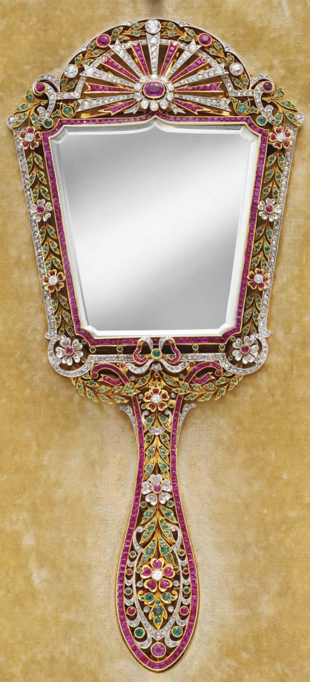 A DIAMOND, RUBY, AND EMERALD HAND MIRROR The shield-shaped mirror within an openwork variously-cut diamond, emerald, and ruby surround of foliate motif, to the tapered handle of similar design, mounted in gold and platinum, 9½ x 4¼ ins.