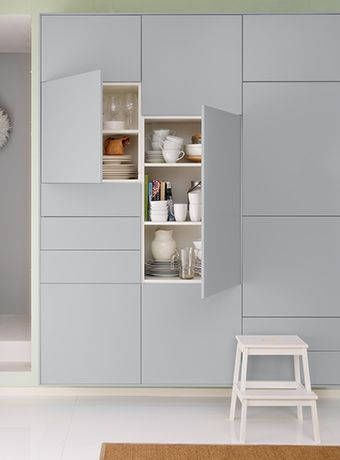 Close-up of same IKEA kitchen cupboards. Two cabinets are open showing contents.