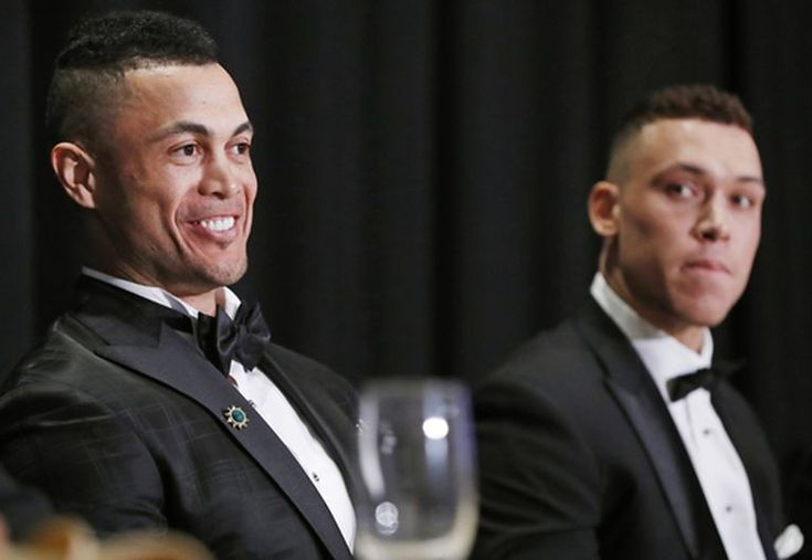 National League Most Valuable Player Giancarlo Stanton, left, and American League Rookie of the Year Aaron Judge listen too speakers during the New York Chapter of the Baseball Writers' Association of America annual dinner in New York, Sunday, Jan. 28, 2018, where both picked up their awards. (AP Photo/Kathy Willens)