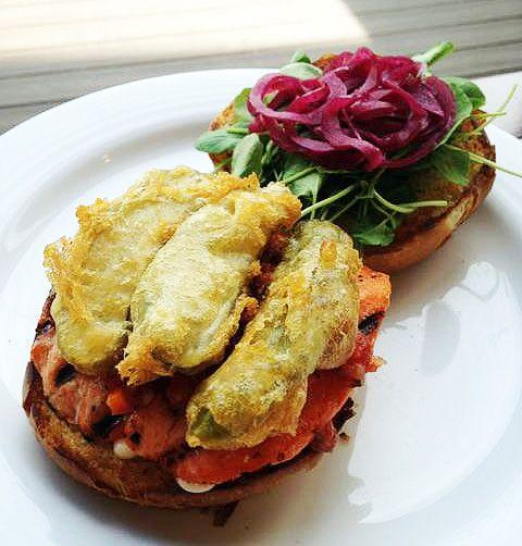 Salmon Burger: cocktail sauce, battered pickle, watercress, pickled onion, mayo on sesame bun | New Menu Item | New Menu Launch | Pier 73 | YVR