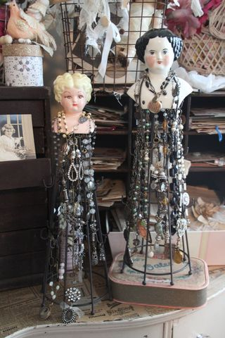 A great jewelry display. Small (porcelain?)  doll heads mounted on wire towers with wood bases.