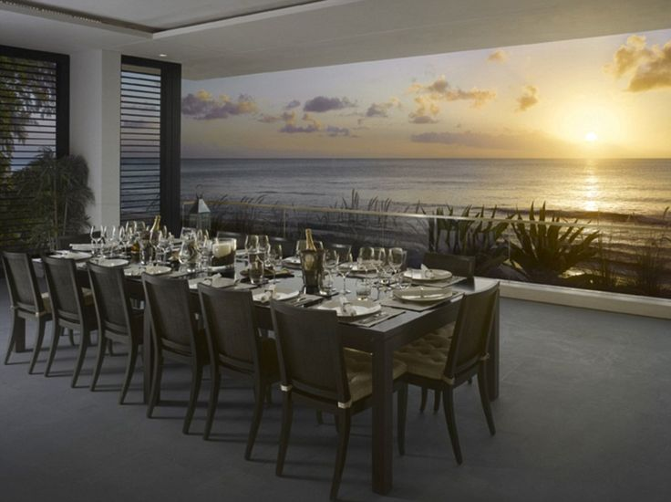 In a grand reception room is a dining table that seats 14 people, with views over the oce...