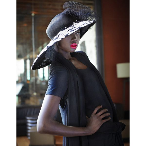 Large black sinamay hat with extended brim. French draping on the brim in black and white floral makes this hat a stand out race piece.