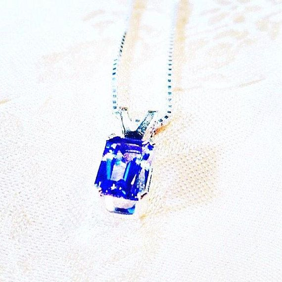 A beautiful 1CT emerald-cut tanzanite shows off its flawless appearance in the simple elegance of sterling silver and hangs on an 18 sterling sterling silver box chain. Great example of ideal tanzanite color. About tanzanite. A December birthstone, tanzanite is said to be a stone