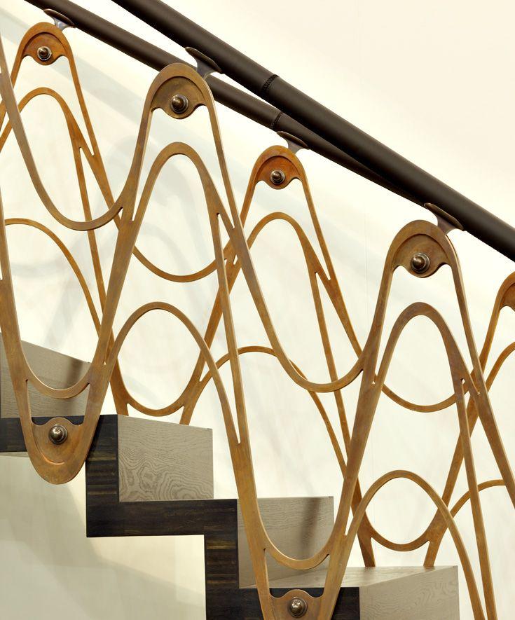 ST890 Łukowe schody dywanowe wykonane z dębu wędzonego. Balustrada z cortenu i mosiądzu, pochwyt wykończany skórą. Projekt – TRĄBCZYŃSKI