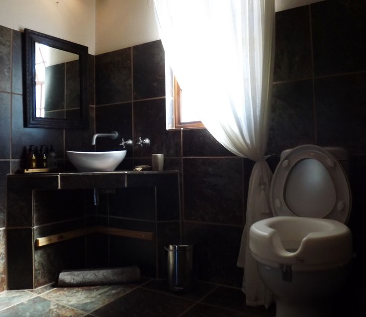 En-suite bathroom; Toilet raiser, shelf removed from under the vanity and miroor lowered.