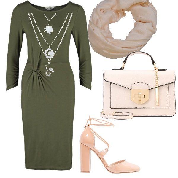 La delicatezza del color cipria degli accessori si accosta all'intensità del verde bosco del vestito aderente con motivo sul davanti. Gli altri elementi che compongono l'outfit sono un foulard da annodare al collo, scarpe con tacco alto, borsa a mano e una collana con tre ciondoli: un outfit che associa eleganza e semplicità.