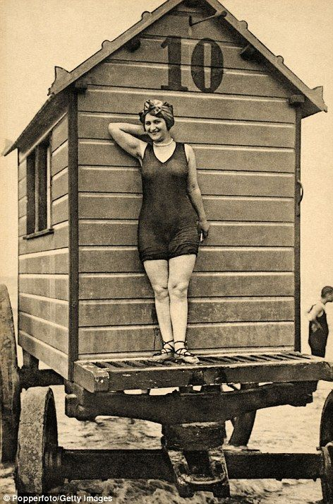 Bathing beauties show of the must have beach fashions in front of a portable bathing hut in Ostend, Belgium, circa 1920