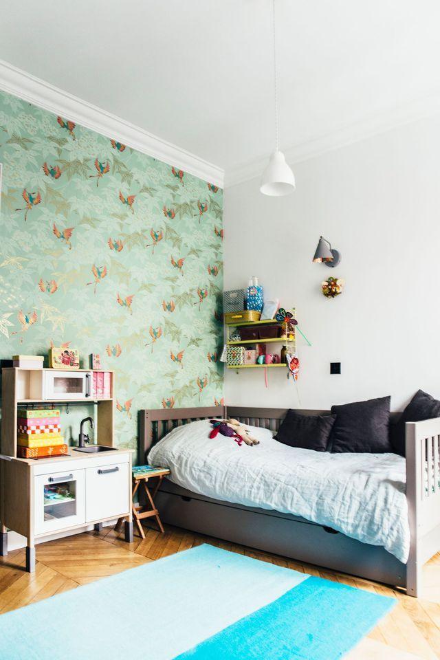 La chambre d'enfant ose le papier peint à motifs oiseaux.