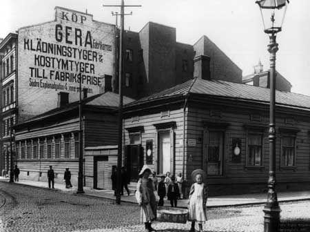 Iso Roobertinkadun ja Yrjönkadun kulma 1907. Pyykin peseminen ahtaissa kaupunkiasunnoissa oli hankalaa ja työn tekivät yleensä pyykinpesijät . Tytöt ovat viemässä puhdasta pyykkiä asiakkaalle. Kuva: Signe Brander.