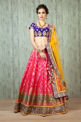 Sangeet Lehengas - Indigo and Hot Pink Silk Lehenga | Hot Pink Banarasi Silk Lehenga with Green and Gold Print and Zardosi and Gota Border Work, Indigo and Gold Raw silk blouse, Yellow net dupatta with indigo colored border | WedMeGood #wedmegood #hotpink #banarasi #silk #raw #silk #indigo #yellow #zardosi #gota