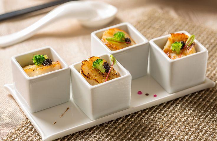 翡翠干貝泥佐魚子醬。 原名為翡翠豆腐,食材中卻沒有豆腐,而是由毛豆及青豆攪拌成泥所製成。看似單純的一道菜,卻需要深厚的料理功力,首先食材本身的要求極高,若沒有恰巧成熟的青豆,色澤難以在繁複的做法中保持青翠如滴的原色,為了增添豆香,特別使用飽滿的毛豆仁,另外搭配品質極佳可生吃的北海道干貝,將雙面上色煎至五分熟後,上方綴以魚子醬。將兩種豆類攪拌成泥狀,費時半小時的反覆添油炒制以避免黏鍋,最後還要做到不見油,火侯控制的功力需非常成熟,道道程序都不得馬虎,起鍋前嗆入花雕酒及香油拌勻,鮮香可口的滋味,搭配干貝迸出的鮮美滋味,同時魚子醬散發出來的海洋氣息充滿整個口腔,是道奢華令人陶醉不已的開胃小菜。 #翡翠干貝泥佐魚子醬 #主廚推薦 #粵菜廳