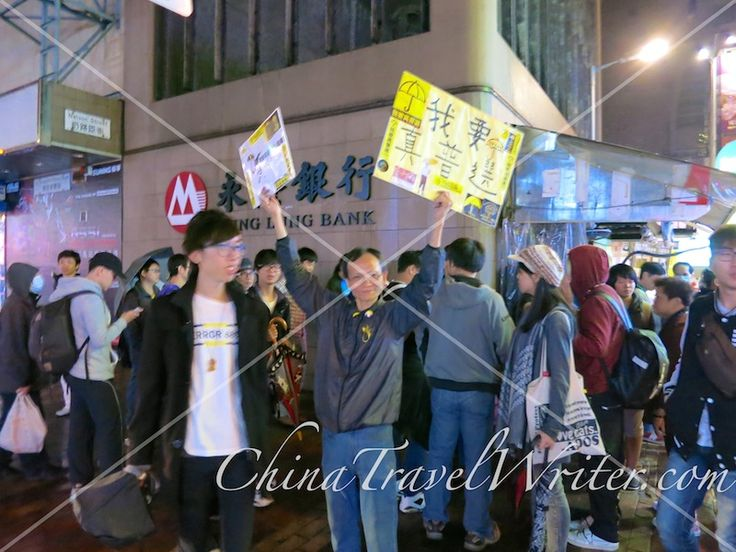 "#OccupyHK protesters in #Mongkok walk along the sidewalks in a ""shopping"" demonstration at night. Police follow them and stand on the street, ready to prevent any of them from taking the street. Chief Executive CY Leung had called for residents hit the shops after the Mongkok street occupation was cleared."