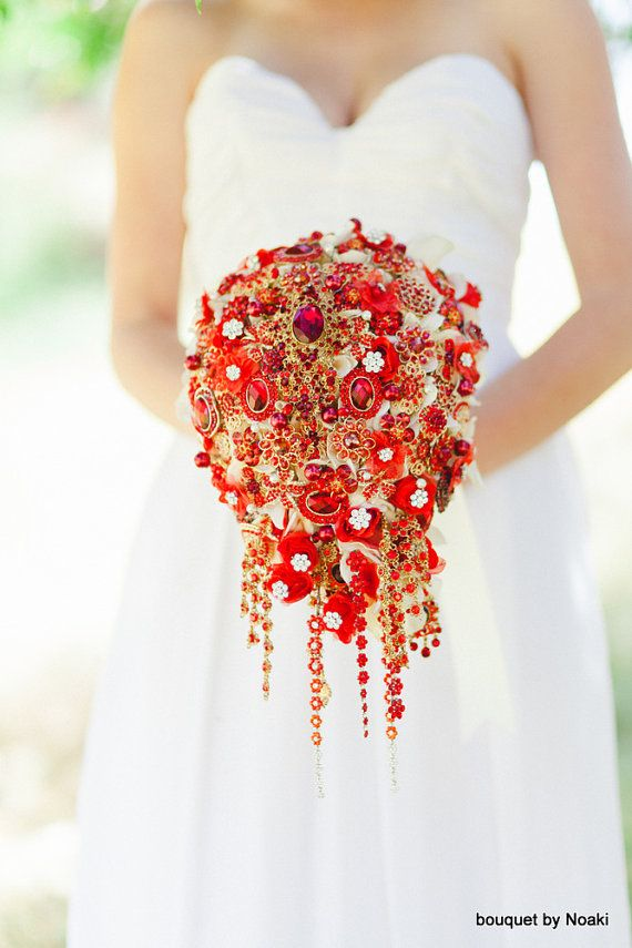 This stunning wedding bouquet features a mix of red rhinestone jewellery set in gold and handmade red roses against a bed of ivory cloth flowers. Pearls and faceted glass beads have also been hand-wired into the bouquet and rhinestones have been attached to the petals of the cloth flowers. The bouquet measures 8 inches across and about 15 inches long.