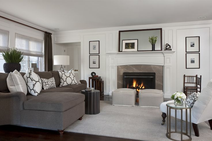 Chic living room with white tufted slipper chair and round glass-top accent table over gray rug. Pair of light gray cube ottomans sit in front of traditional fireplace with gray stone surround. Stacked art in gallery frames flank tall fireplace with mirror, decorative wall moldings and decorative accents.
