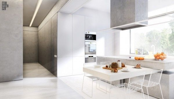 In the kitchen, a small breakfast table and heavy slab countertop benefit from streams of natural light.