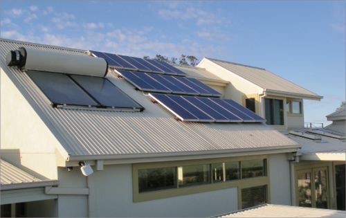 A suburban house with photovoltaic solar panels and a solar hot water system on its roof