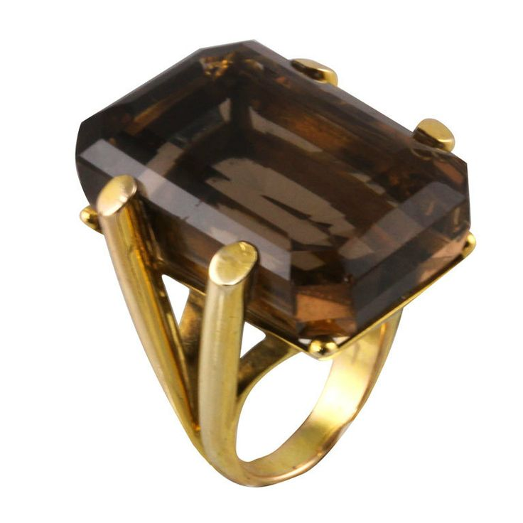 Glamorous Smoky Topaz Retro Ring  Italy  1970's  The ring is in 18k yellow gold and is a retro mounted very large 54 carat Smokey Topaz. The ring is a split shank tubular mounting and the stone is a step cut rectangular shape.  Price  $3,200
