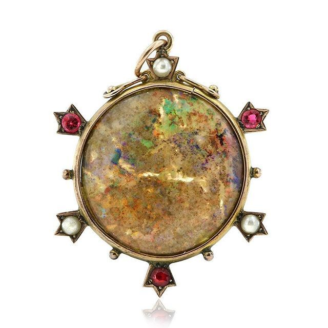 A one-of-a-kind Antique pendant featuring double flat cabochon, treated opal matrix as the centrepiece of this antique photo frame. The frame is surrounded with 3 imitation half pearls and 3 garnet topped red doublets. Circa 1900-10, make this piece yours
