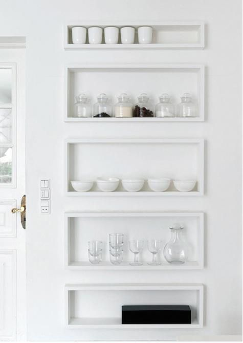 Shallow shelves hold a collection of glassware and ceramics.