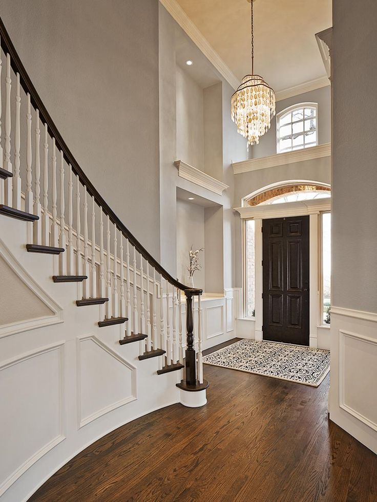 This stunning foyer features light gray walls paired with dark brown hardwood floors and a traditional spiral staircase. Neutral wall panels add a classic touch, while a glamorous chandelier finishes off the look of the space.