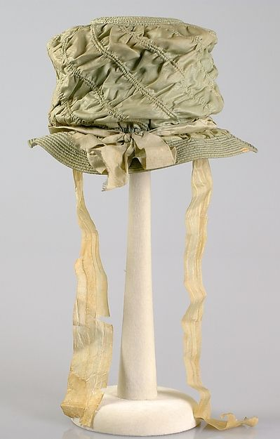 1820 silk Bonnet with decorative stitching.  It looks somewhat like a feminine version of a man's top hat.  This is a lovely shade of sage green with gold silk bonnet ribbons