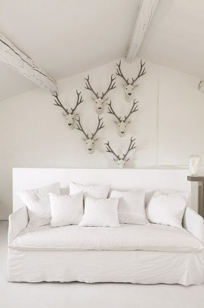 La touche d'originalité : les têtes de cerfs dans le salon blanc immaculé. Plus de photos sur Côté Maison http://petitlien.fr/82u9