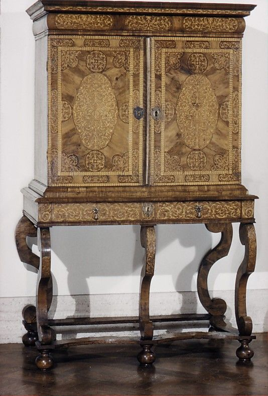 Cabinet on stand Date: ca. 1695–1700 Culture: British Medium: Walnut, holly marquetry, pine carcass, oak drawers, brass hardware Dimensions: H. 64-3/4 x W. 39-1/4 x D. 30-3/4 in. (164.5 x 99.7 x 78.1 cm) Classification: Woodwork