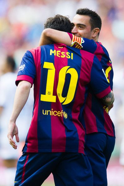 Lionel Messi of FC Barcelona is congratulated by his teammate Xavi Hernandez after scoring the opening goal during the La Liga match between FC Barcelona and RC Deportivo La Coruna at Camp Nou on May 23, 2015 in Barcelona, Catalonia.