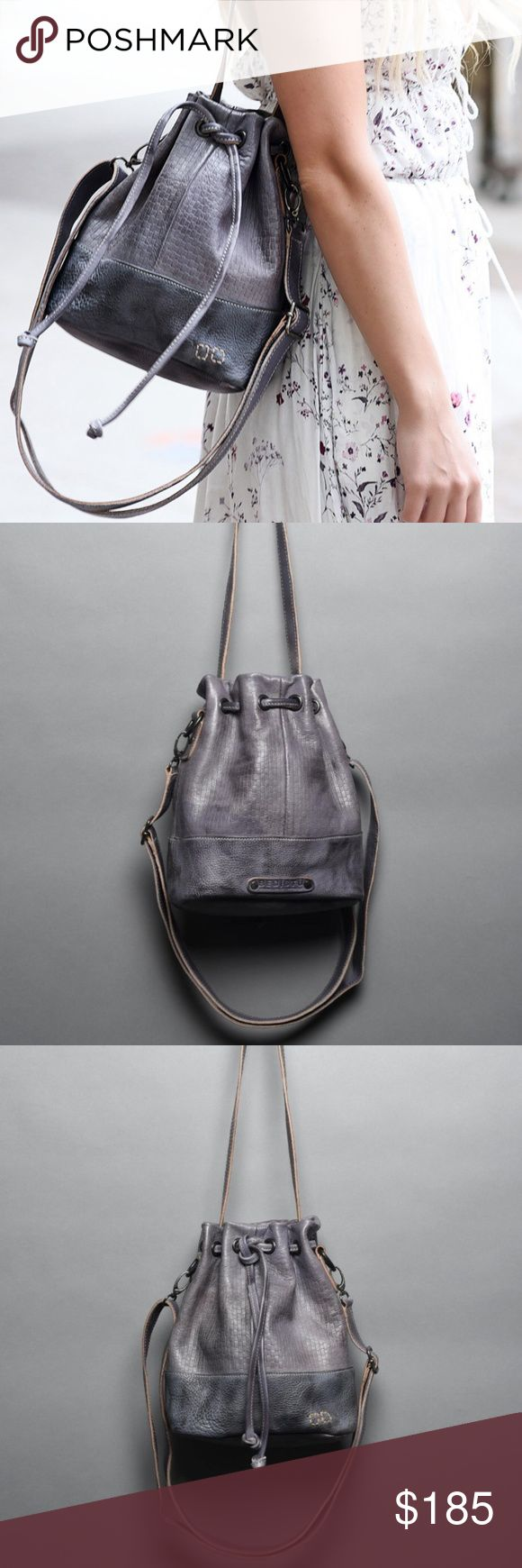 "Bed Stu Abbeville Leather Crossbody Bucket Bag NWT This beautiful leather bucket bag can be worn as a crossbody or as a shoulder bag.  New with tag.  The crossbody strap is adjustable and removable.  The shoulder strap can be hidden inside of the bag.  The color name is ""Smoke Blue"".  It looks more like a gray color.  Chrome free, vegetable tanned leather.  Canvas lined, w/ 1 zipper pocket, & 2 slip pockets.  Measures 10"" H, 11.5"" W, 5"" D, with an 11.25"" drop. Bed Stu Bags"