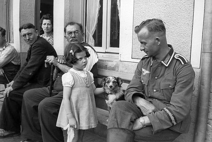 A curious little French girl gazes upon a German soldier of the Wehrmacht who is settling down for a well-earned bout of downtime following the German Reich's victory of unprecedented speed and tactical precision over its neighboring western nations. France. Summer, 1941.