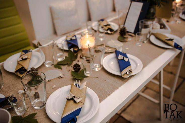 Rustykalne, granatowo - złote jesienne wesele. Stół widziany z góry, biało-niebieskie kwiaty, ekologiczny bieżnik, złote liście, szyszki, żołędzie i kamyczki. Na środku kompozycja kwiatowa w słoiku. / Rustic, wedding, natural, eco, table, decoration, fall, autumn, ideas, white, gold, navy, blue, flower, centerpieces, rocks, cones, acorns, leaves, candles, mason jar.