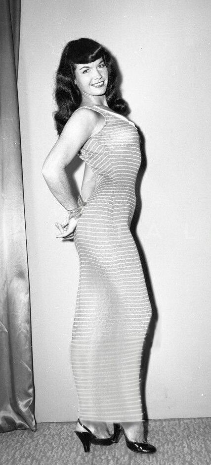 99c29831c99 Bettie Page wearing a long striped dress with her hands tied behind her back