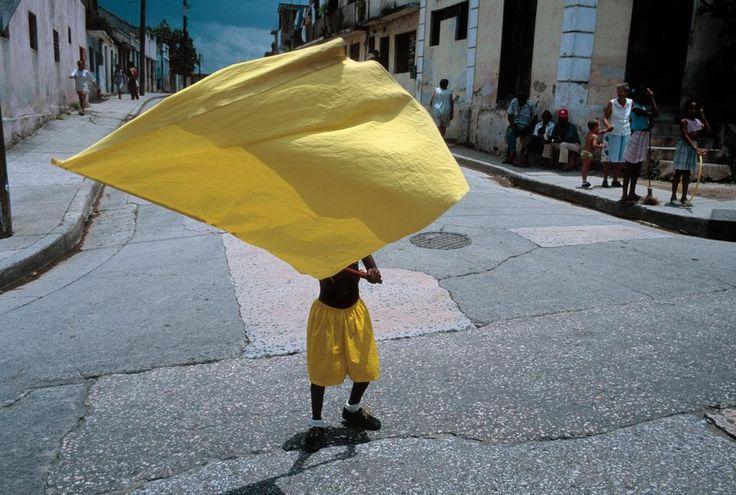 David Alan Harvey CUBA. Santiago de Cuba. 1998. A young boy carrying a yellow banner during carnival.