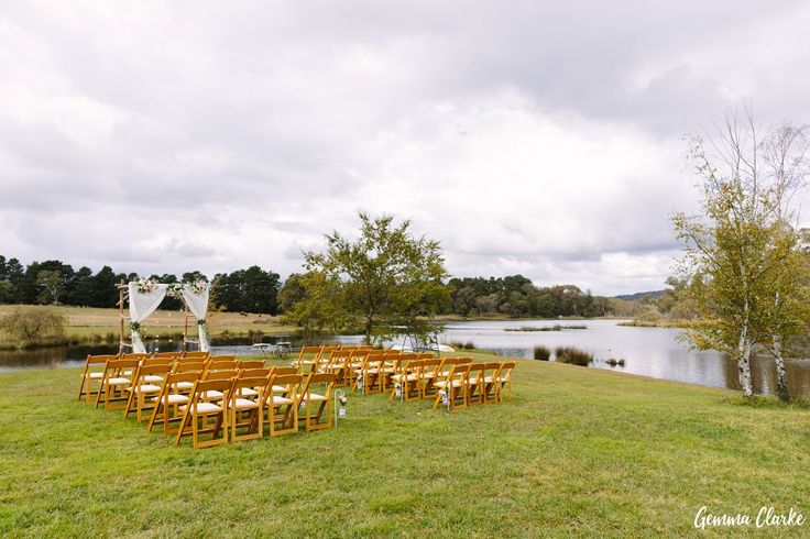 Ceremony setup with chairs, an arbour with floral styling overlooking a beautiful lake at this Autumn Southern Highlands Wedding