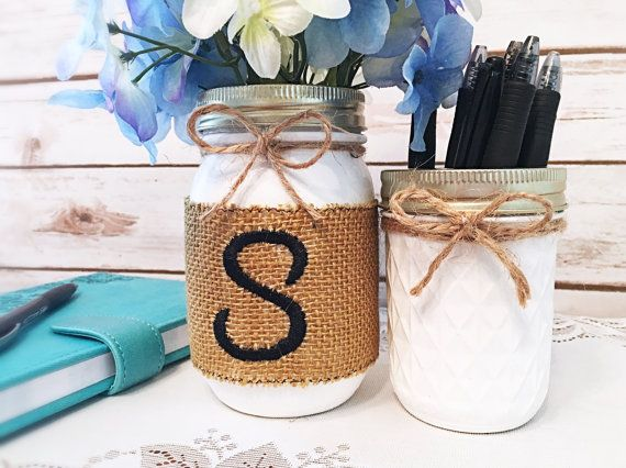 Mason Jar Organizer--Mason jar organizers are elevated to a rustic desk accessory set with the addition of an embroidered initial. This desk accessory set captures the rustic elegance of country decor with the use of satin paint, a simple bow, and a monogrammed burlap sleeve.