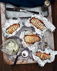 Grill-Baked Potatoes with Chive Butter Recipe on Food & Wine - They're layered with pats of chive and sour cream butter, then wrapped in foil and grilled until soft and delicious.