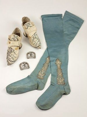 "Blue socks with embroidered ""clocks,"" white shoes with embroidery, both British. Silver-tone buckles with clear gems (diamonds?), French. All mid-18th century."