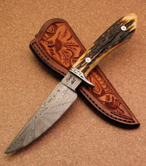 Sole authorship work by Jerry Fisk. Amber Stag mortise handle. Engraved stainless steel guard and pins by Jerry. Dogstar damascus blade. Comes with Kenny Rowe sheath. Made is 2007. Damascus is 1084 and L6 which is double tempered.