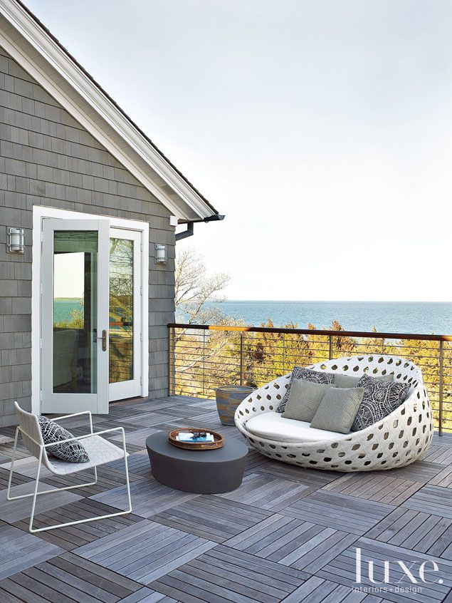 Island Living: Perfect Getaway For a Manhattan Family --- THE BALCONY - The master bedroom's balcony sits peacefully above the treetops and boasts ocean views uninterrupted by the railings (placed horizontally for this reason). A B&B Italia Canasta chair and Janus et Cie Trennza lounge chair sit atop 24-by-24-inch wood deck tiles by Bison.