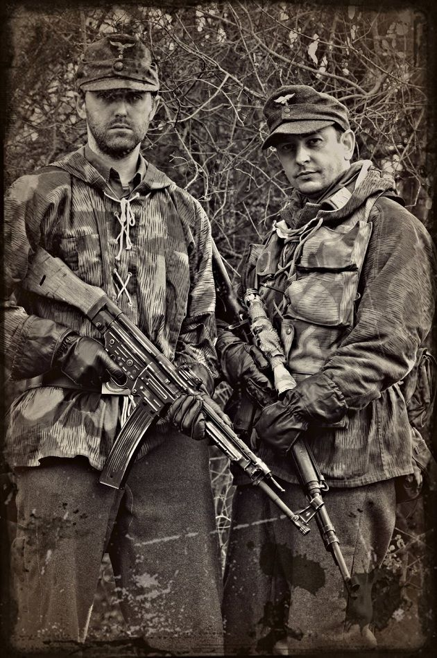 Two Luftwaffe re-enactors pose with a SturmGewehr 44 and a sniper's rifle. Their camouflage smocks are of the Splinter pattern (Splittertarn)