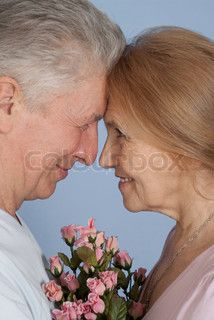 Happy Caucasian elderly people stand together with the flower