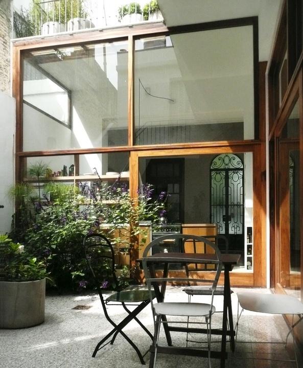 Una casa de más de 100 años en Palermo, Buenos Aires, remodelada. En la foto se ve en el fondo la puerta de entrada original de hierro forjado, una maravilla.