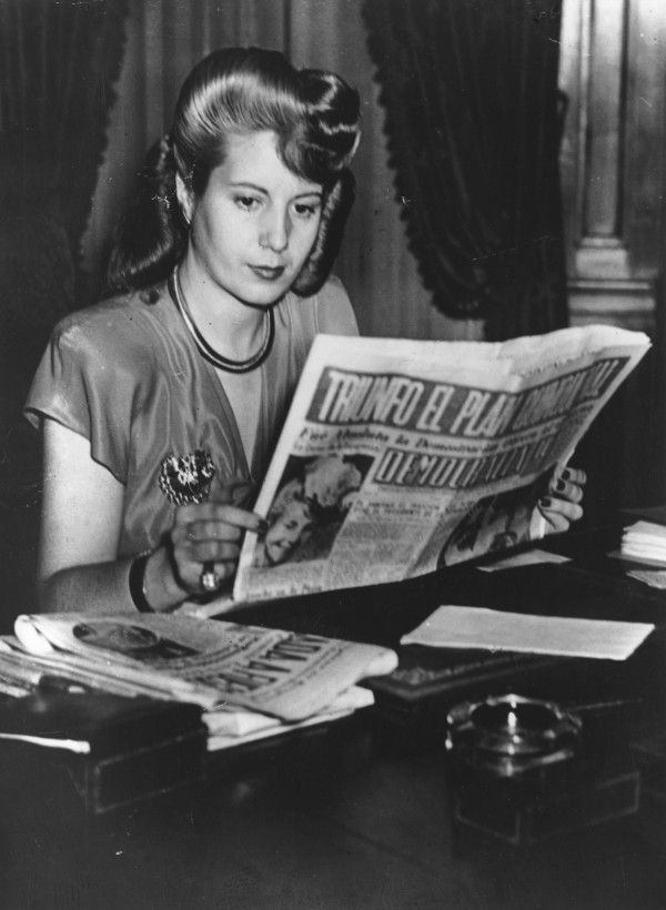 Eva Perón (1919-1952), wife of Argentinian dictator Juan Perón, reads a copy of 'Democrazia,' the newspaper she owns. 10th April 1947. With the aid of his popular wife, Eva Duarte de Perón, Juan Domingo Perón converted trade unions into a militant organization, known as the descamisados or shirtless ones, along fascist lines.