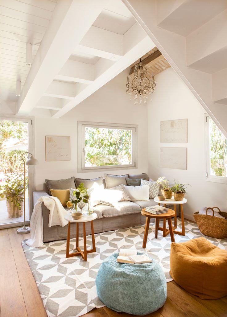 26-Salón con vigas blancas, alfombra geométrica, pufs, sofá gris y mesitas redondas 00425991