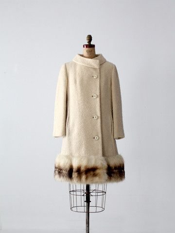 A 1960s vintage boucle wool coat with fox fur trim by Fairweather. The cream wool coat features an off-center closure, princess seams, and hand-warming pockets. Fox fur trims the hemline. The interior