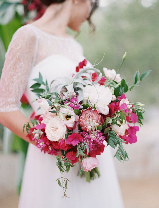 blush, ivory and fuchsia bouquet featuring protea, garden roses, peonies, clematis, air plants and bougainvillea by Peony & Plum